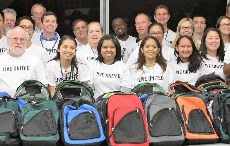 Employees Join Forces to Stuff the Bus with 100 Backpacks