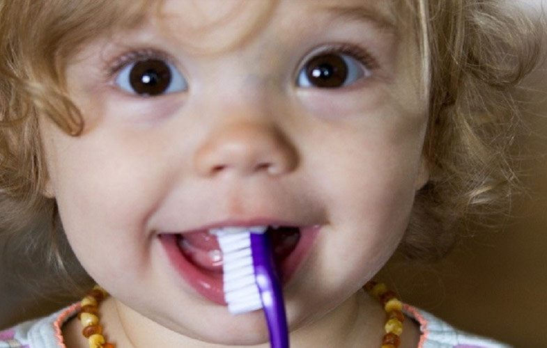 little girl holding toothbrush in her mouth