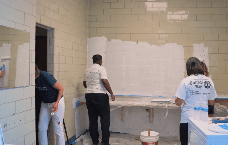 volunteers paint school laundry room