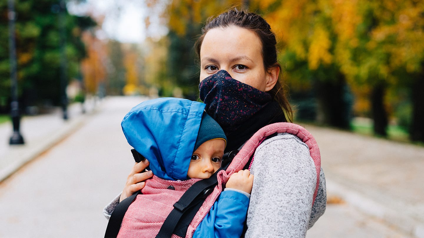 masked woman holding baby