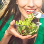 Smiling woman eating a salad